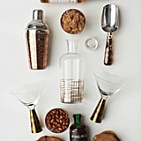 Here's everything you need to complete a similar look:   Copper cocktail shaker ($13) Martini mix ($10) Ice scoop ($8) Wire basket ($15) Patterned candy jar ($4) Glass decanter ($13)  Source: Style Me Pretty