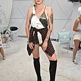 Ireland Baldwin wearing white overalls, a flannel, and over-the-knee boots at the Winter Bumbleland.