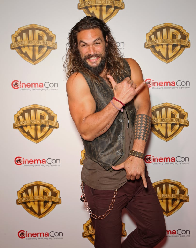 """Jason Momoa is known for many things: his long, beautiful hair, his incredible acting chops, his shirt-busting muscles, and of course, his laid-back personality. So, it shouldn't come as a surprise that his go-to pose is a shaka sign. The friendly gesture, which is often associated with surf culture and the actor's native Hawaii, is most commonly known to mean """"hang loose."""" And he certainly loves throwing the sign whenever he gets a chance. Whether he's on the red carpet or he's grabbing a beer with friends, see all the times he made you want to kick back and hang ten.       Related:                                                                                                           Jason Momoa's Instagram Is So Full of Gems, You'll Feel Like You've Won the Hotness Lottery"""