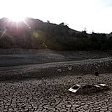 A car sits in the dried earth at the Almaden Reservoir.