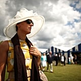 A woman dons a hat at the races.