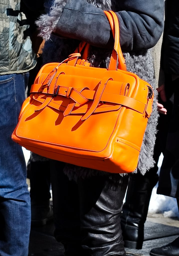 An orange Reed Krakoff tote shone against a dark gray coat and black leather pants.