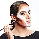 Place a dark brown grease-based color over the forehead, on the jaw, and the outside of the nose (similar to contouring). Blend with a sponge and set with powder.
