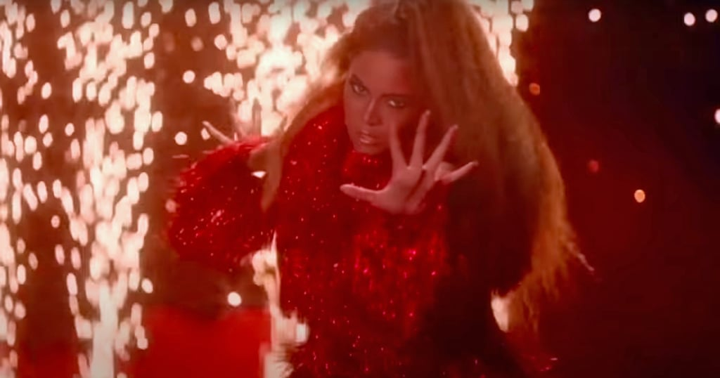 Beyoncé wears a red fringed dress.
