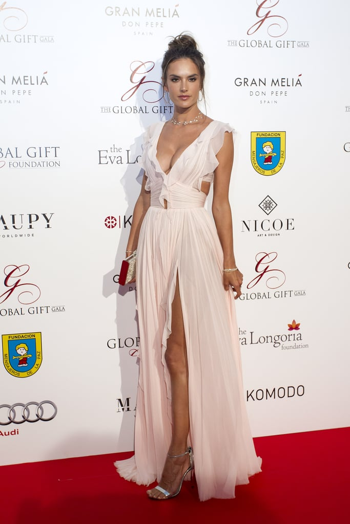 After an extended stay in Mykonos, Alessandra Ambrosio stylishly jetted over to equally as sunny Spain for the 2016 Global Gift Gala in Marbella. The Brazilian Victoria's Secret Angel turned heads on the star-studded red carpet in a soft pink J. Mendel gown with a plunging neckline, a sexy slit, and all kinds of dainty ruffles throughout. Alessandra paired the stunning number with Messika jewelry, silver heels, and a matching clutch, resulting in a princess-worthy look — all that was missing was a tiara over her wispy topknot. Keep looking to see even more pictures of Alessandra at the event (including one with Eva Longoria!), and then take a look through her best street style this year.
