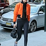 For a pop of color, Gigi styled her black leggings with a bright orange bomber jacket.