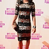 Gabby Douglas shined on the red carpet in a black and gold sequined dress and peep-toe ankle booties.