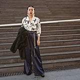 Navy trousers feel exciting with a printed blouse and statement earrings.