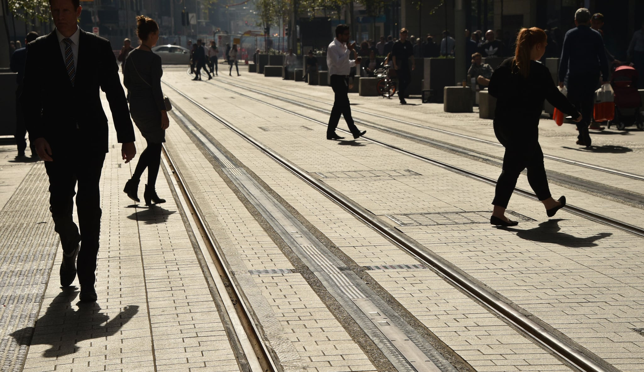 Pedestrians walk across the new light railway in the central business district of Sydney on May 8, 2018 as the Australian government prepares to release its 2018/19 budget later in the day. (Photo by PETER PARKS / AFP)        (Photo credit should read PETER PARKS/AFP/Getty Images)