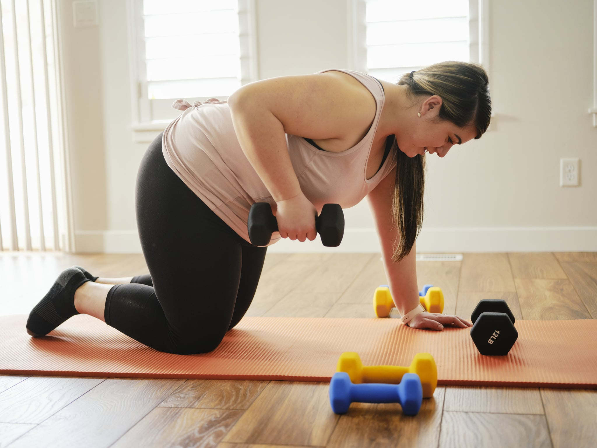 A woman exercising in her home with hand weights.