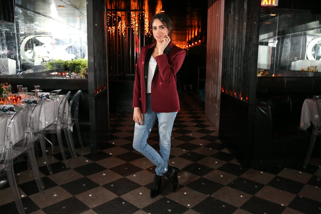 Wearing a pair of light-wash skinny jeans with a burgundy blazer and black boots.