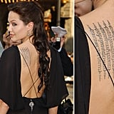 "Angelina Jolie's back features Buddhist text. It's reportedly a recitation meant to protect her and son Maddox. It reads, ""May your enemies run far away from you. If you acquire riches, may they remain yours always. Your beauty will be that of Apsara. Wherever you may go, many will attend, serve and protect you, surrounding you on all sides."""