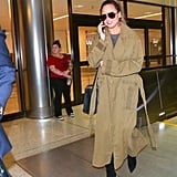 Chrissy at LAX wearing a camel-hued trench coat, gray shirt, and suede boots.
