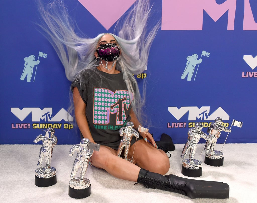 """Lady Gaga was omnipresent at the 2020 MTV Video Music Awards on Sunday. One moment she was arriving in an avant-garde spacesuit, and the next she was honouring her friendship with Ariana Grande in a heartfelt speech before taking the stage with the fellow pop star to perform """"Rain on Me"""" in a truly otherworldly Chromatica medley. (I'm tired for her.) Along the way, she also picked up almost as many awards as the amount of vastly creative face masks she wore.  Seriously though, Gaga dominated in the following four categories: artist of the year, song of the year, best collaboration, and best cinematography. She also became the first-ever recipient of the award show's newly invented Tricon award, which, well, honours triple-threat icons. Gaga then solidified her Tricon status — it'll catch on? — by dramatically posing with her five moon person trophies in an MTV t-shirt with inexplicable wind in her hair. Look ahead for the photographic proof, as well as other standout moments from Gaga's busy evening.       Related:                                                                                                           Lady Gaga Brought Major Moon Person Energy to the VMAs, and We Need Space to Take It In"""