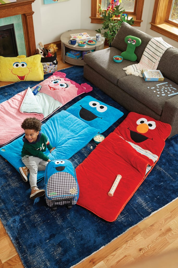 Furry Big Bird Sleeping Bag ($129), Furry Abby Cadabby Sleeping Bag ($129), Furry Cookie Monster Sleeping Bag ($129), Furry Elmo Sleeping Bag ($129), Letter I Throw Pillow ($29), and Cookie Monster Rolling Luggage ($59)