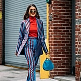 Camila Coelho's striped suit really pops off of her matching red shirt and blue bag.