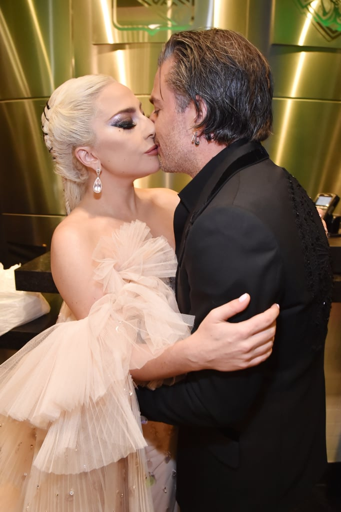"Lady Gaga may have walked the Grammys red carpet solo on Sunday, but you better believe her fiancé Christian Carino was there to support her on her big night. Following her chill-inducing performance of ""Joanne (Where Do You Think You're Goin'?),"" Mother Monster was photographed backstage getting cozy with the talent agent, marking the couple's first official appearance since they got engaged this past Summer. Gaga is also nominated for two awards tonight, including best pop vocal album, so best of luck to her!"