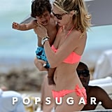 Doutzen Kroes wore a florescent bikini and carried her son.