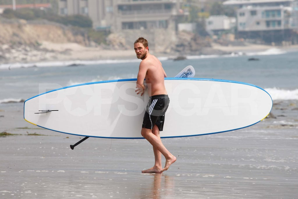 Robert Pattinson carried his paddleboard on the beach.
