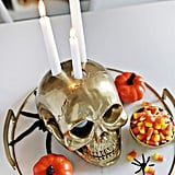 A golden DIY candle-holder skull is spooky but also brings an element of glam rock to the soirée.