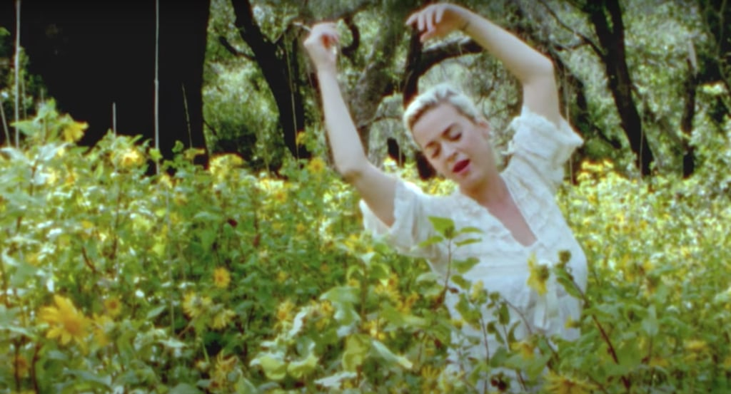 """Katy Perry's music-video outfits never disappoint. Just two months after wowing us with a Midsommar-inspired look for her """"Never Worn White"""" video, the mom-to-be went a decidedly more pared-down route for her latest single, """"Daisies."""" At the start of the ethereal music video, Katy frolics through a yellow-flower-covered forest wearing an off-white slip dress with lacy detailing and polka-dot stitching. She styles the vintage-looking gown with a long, matching kimono, both of which she removes entirely before wading into the waters of a babbling brook. The video then cuts to a new scene — and a new though similar outfit. Katy is standing atop a rock at sunset in a shorter off-white slip dress and cover-up flowing in the wind. Her growing baby bump is fully on display as she belts out lyrics about the beauty of dreaming and believing in magic. The video could practically double as a CoverGirl ad, because she truly looks """"easy, breezy, and beautiful"""" the entire time. Ahead, take a closer look at both of the dreamy, summery dresses Katy wears in her latest music video.      Related:                                                                                                           Katy Perry Revealed the Look She Would've Worn to the 2020 Met Gala, and It's Oh So Madonna"""