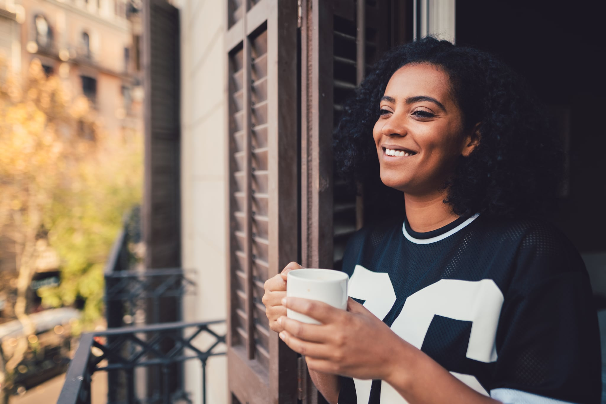 Smiling woman in Barcelona enjoying a cup of coffee at the balcony