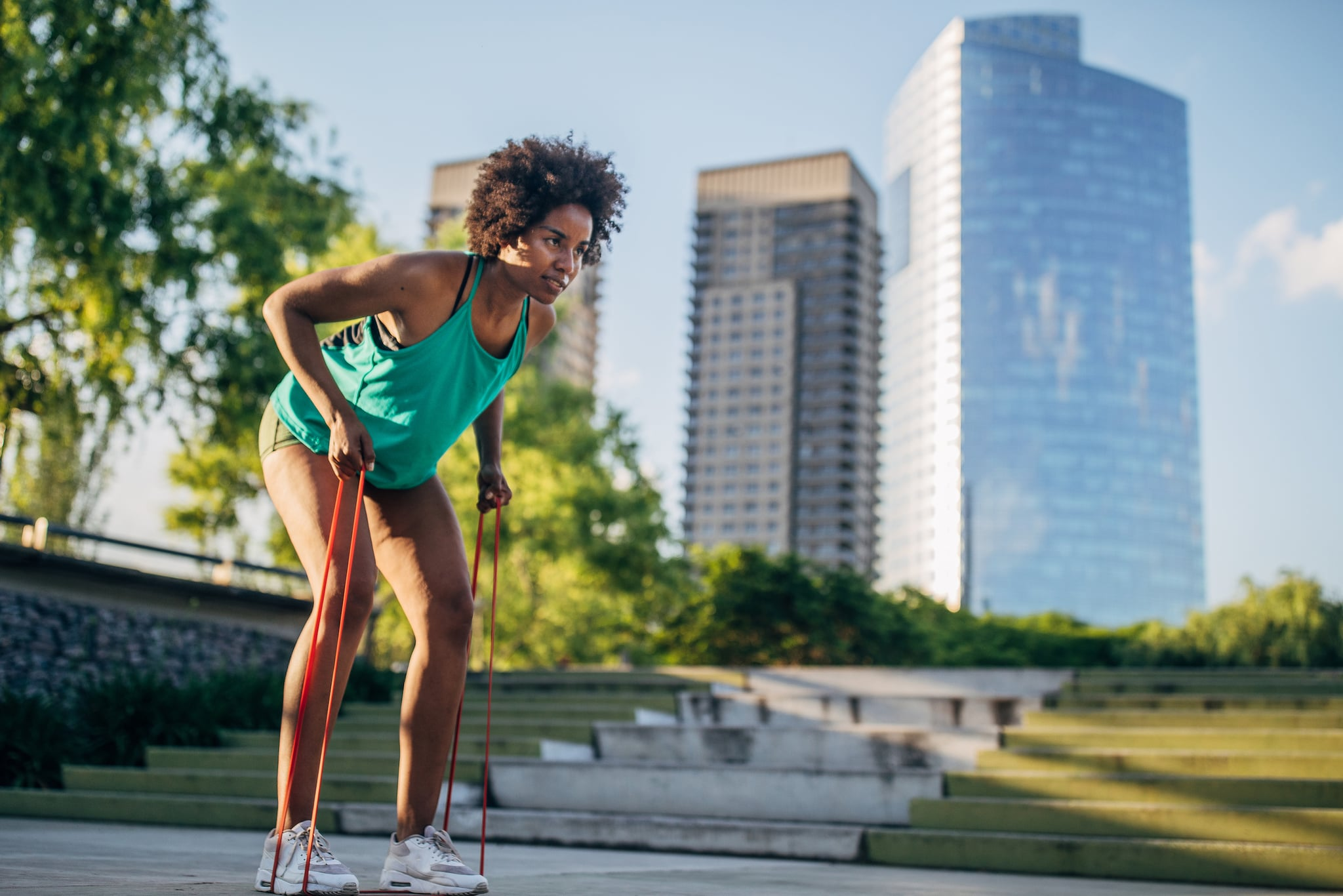 Beautiful young woman exercising outdoor with resistance band