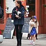 Katie Holmes wore a Balenciaga coat while she walked with Suri Cruise.