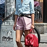 Olivia Palermo tucked a chambray top into printed shorts, then added a studded belt, red bag, and printed ballet flats in NYC.