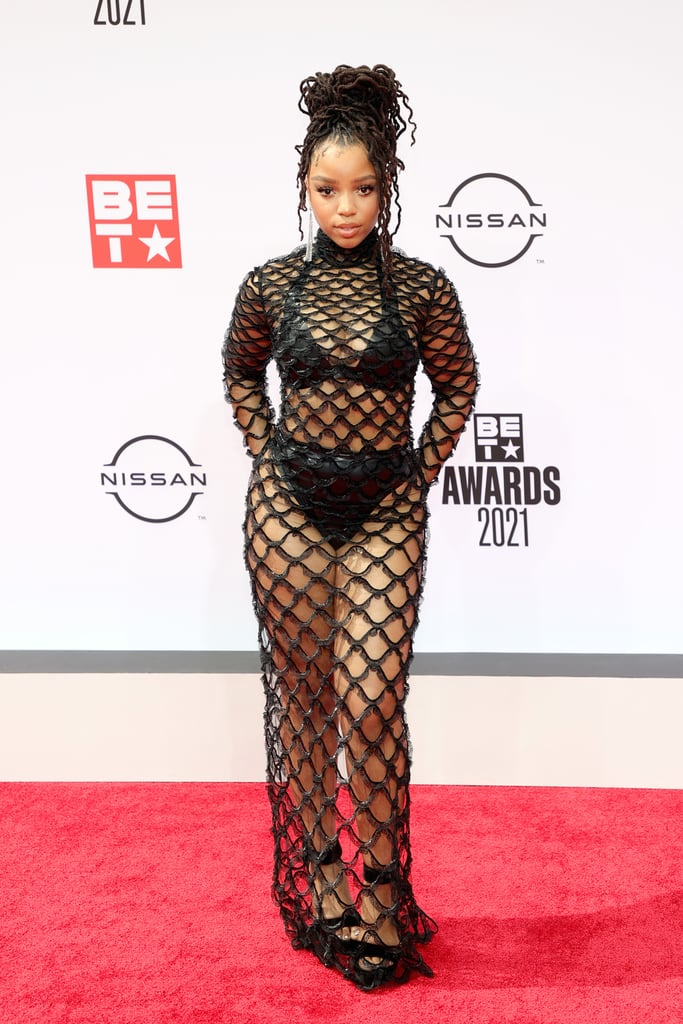 """As soon as Chloe Bailey stepped foot on the BET Awards red carpet, the temperature rose a few degrees. The 22-year-old """"Ungodly Hour"""" singer, who will be presenting during the show, posed for photos in a sheer mesh gown straight from Valentino's runway. Chloe is no stranger to a daring fashion moment, but this dress might be her sexiest yet. She wore a matching black bra and high-waisted bottoms underneath the floor-length, see-through gown and tied the whole look together with heeled sandals and dramatic dangling earrings. Plus, look even closer and you'll notice that each nail in her manicure spelled out her name. No detail was spared! Get a glimpse of Chloe's ensemble from all angles ahead.       Related:                                                                                                           Zendaya Wears Beyoncé's First BET Awards Dress on the Red Carpet — Now That's Respect"""