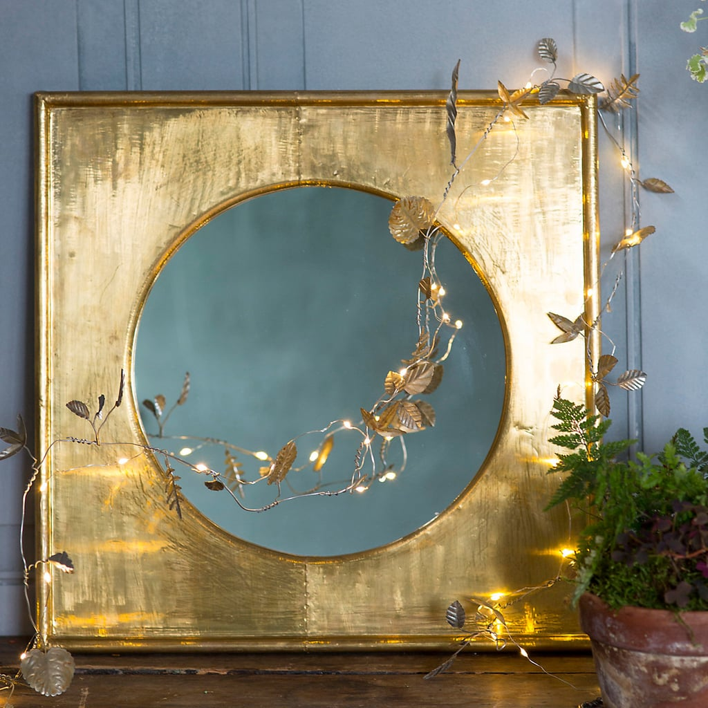 An empty picture frame or beautifully framed mirror looks dazzling with lights draped across it.