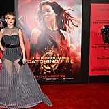 Jennifer Lawrence posed beside her Catching Fire Katniss poster at the film's LA premiere.