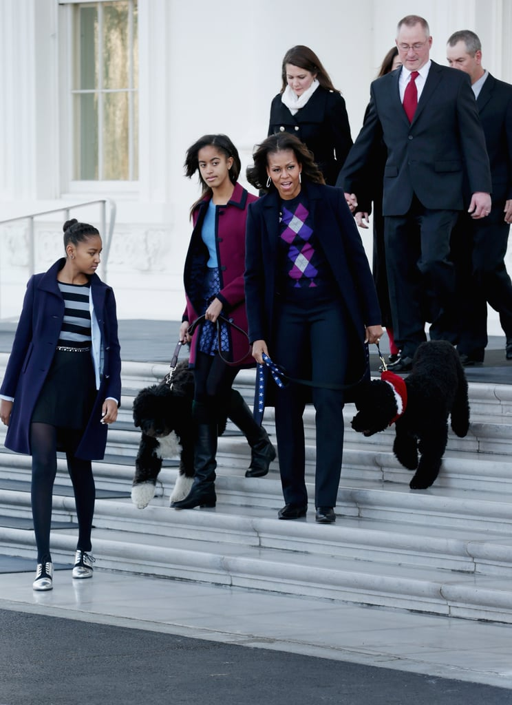 """Michelle Obama had help from a cute crew yesterday at the White House, where she welcomed this year's Christmas tree. Daughters Sasha and Malia were on hand, as well as the first pups! Sunny and Bo were sporting some festive flair and taking in the massive Douglas Fir tree that will go in the White House Blue Room. It's 18.5 feet tall and one of four Christmas trees that will be decorated in the White House. The festive season is givingus all a chance to see just how fast the Obama girls are growing up! They joined their dad on Wednesday for the annual turkey pardon, and in an interview airing in the US tonight, President Obama talked about the sacrifices Michelle and the girls have made for him and said """"Sasha will have a big say in where we are"""" in 2016."""