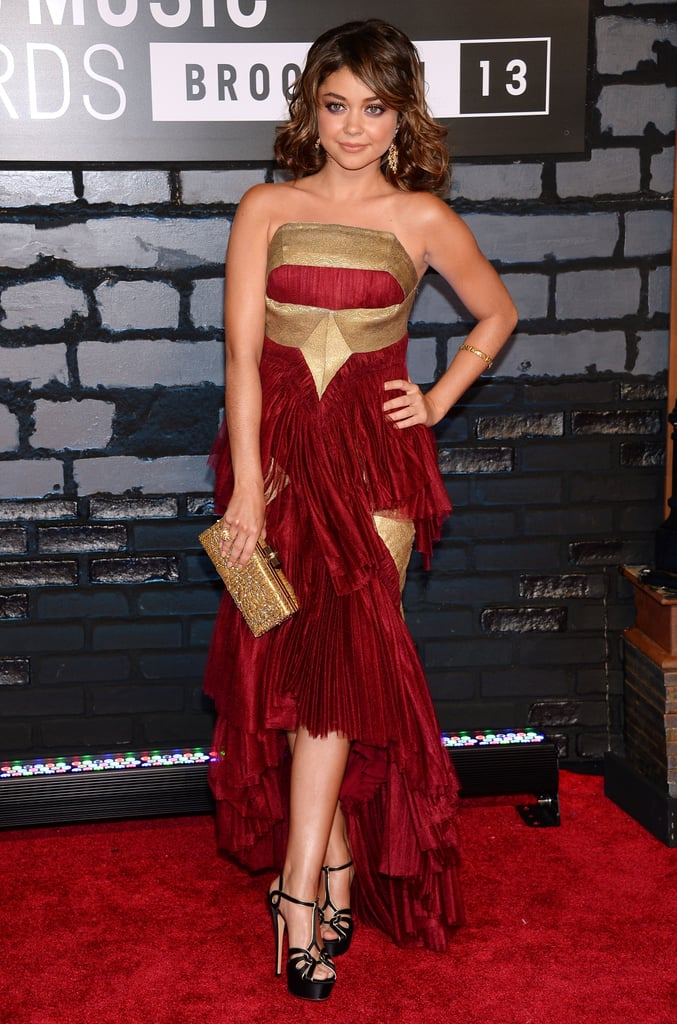 Sarah Hyland was regal in a red-and-gold Marchesa gown. She added a gold embellished clutch and black platform Casadei sandals to the mix to complete her red carpet look.