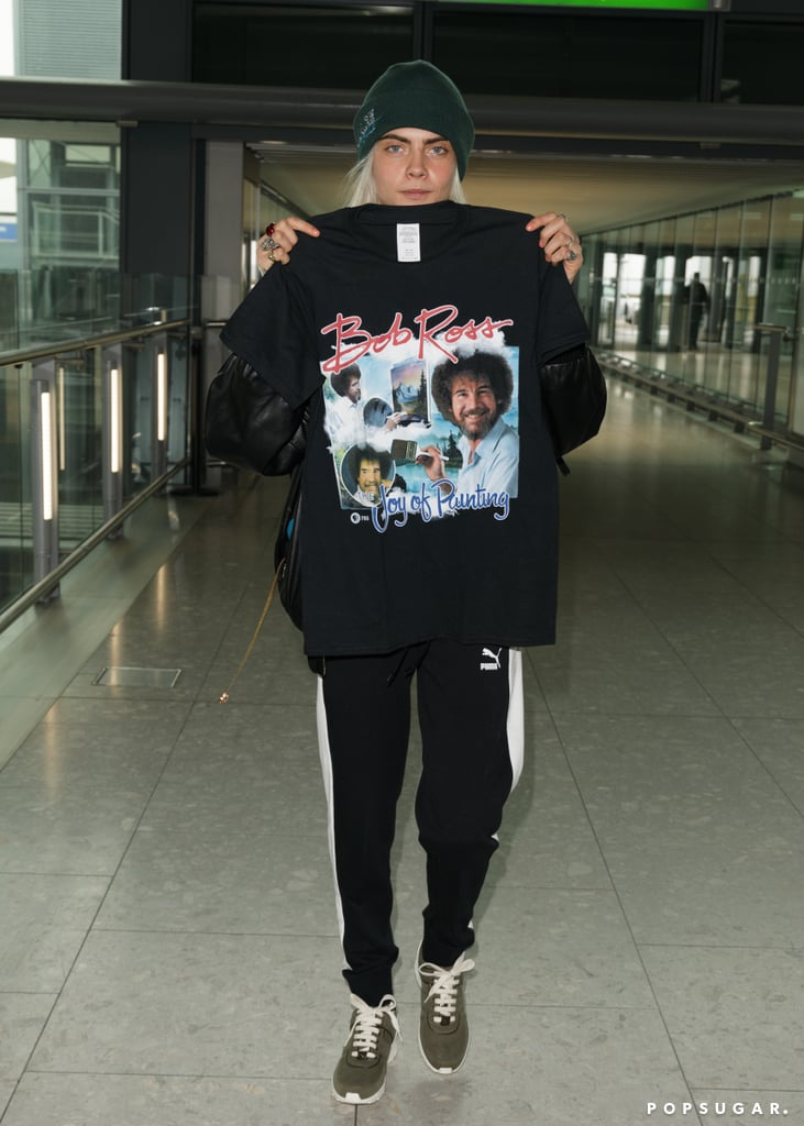 Cara Delevingne Holding up a Bob Ross T-Shirt