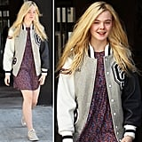 Learn to layer your varsity jacket with  florals for sporty-sweet style like Elle Fanning's.