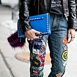 Patched-up denim is the street-cool contrast to a studded clutch.