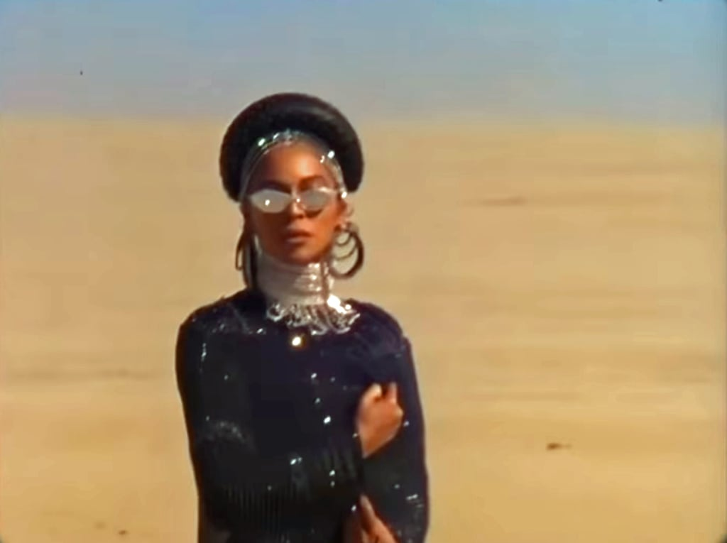 Beyoncé wears a Destiney Bleu catsuit, Area arm ties, necklace, and crystal headpiece, A-Morir sunglasses, and Laurel DeWitt stacked choker and cuffs.