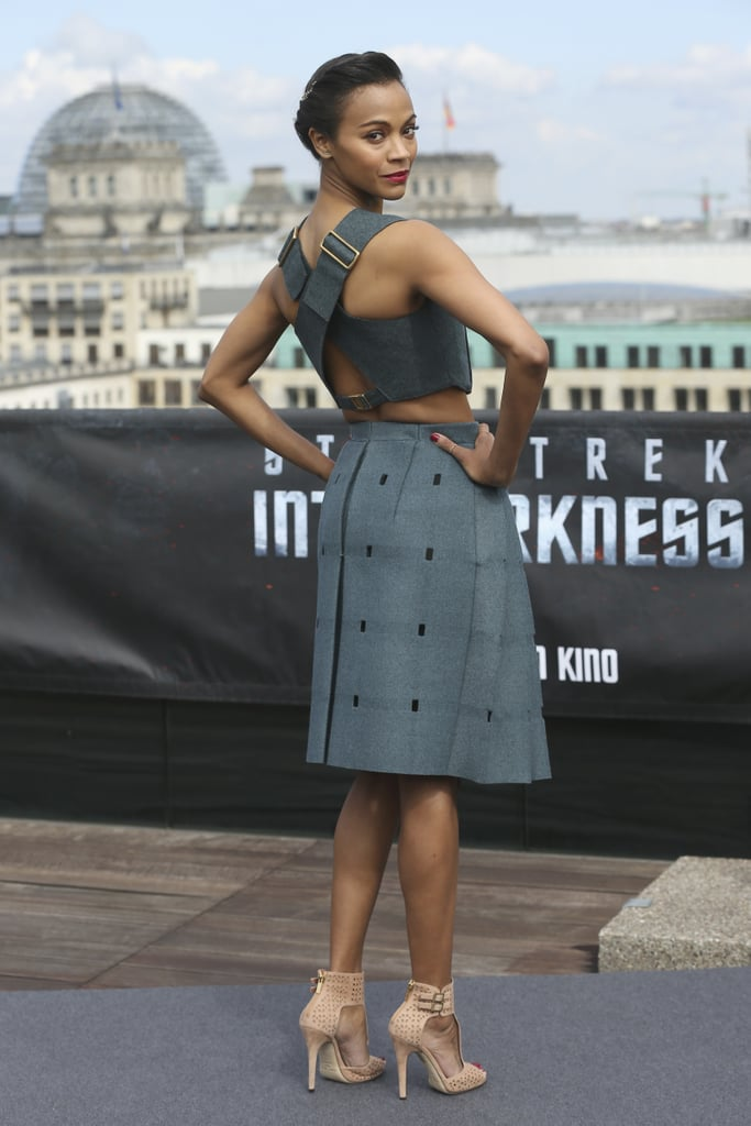 From the back, the sex appeal on Zoe Saldana's Berlin look skyrocketed. The buckle-accented criss-cross straps supplied a tougher, skin-revealing vibe to the grey Calvin Klein crop top and skirt combo.
