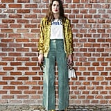 For the Gucci fashion show in February 2017, Charlotte Casiraghi wore a slogan tee, sequin jacket, and wide leg trousers.