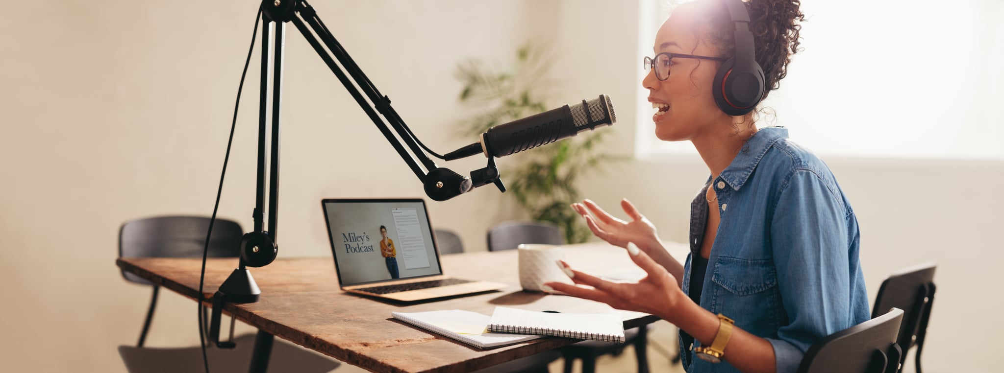 Female broadcasting her podcast from home. Woman wearing headphones talking into a microphone while working from home.