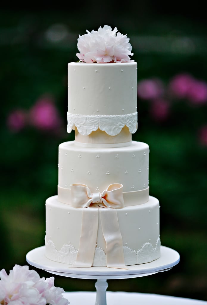 It's got pearls, it's got a bow, it's got a lace-like pattern, and it's got flowers — yet this cake still manages to be sweet and romantic in the simplest way.