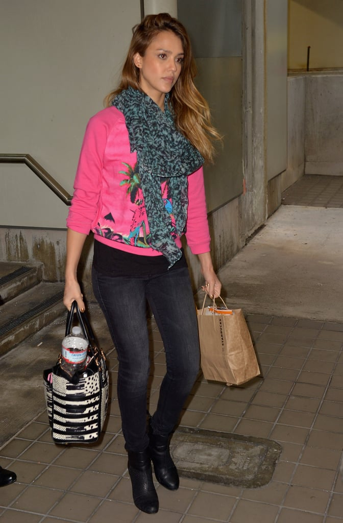 Jessica Alba paired a bright pink sweater and matching scarf with washed black denim and a printed Christian Louboutin tote after touching down in Miami.