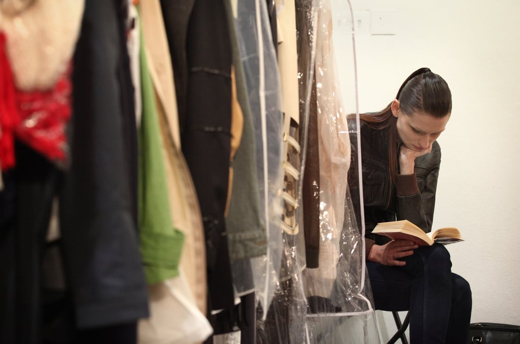 Hidden by a rack of clothing, this model read ahead of The Royal College of Art Fashion Show in London.