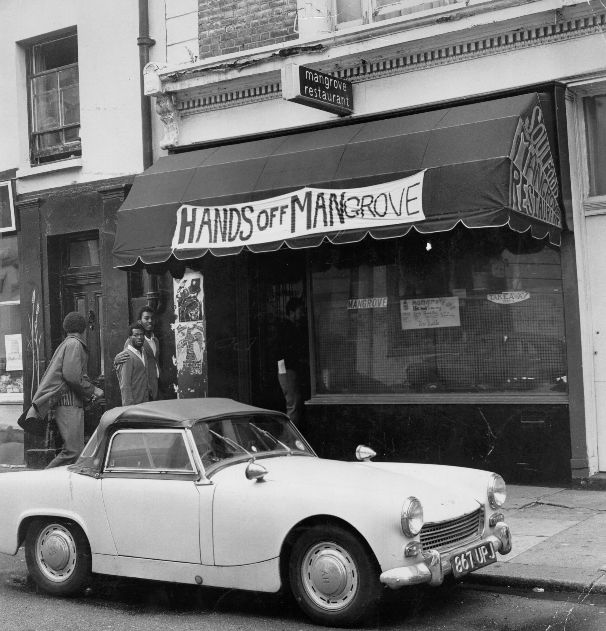 Four men entering the Mangrove, a Caribbean restaurant on All Saints Road, Notting Hill, London, 10th August 1970. The restaurant, seen here with a banner reading: 'Hands Off Mangrove' above it, has been repeatedly raided by the police in the last year, prompting a protest march to be organised by local residents. (Photo by Evening Standard/Hulton Archive/Getty images)