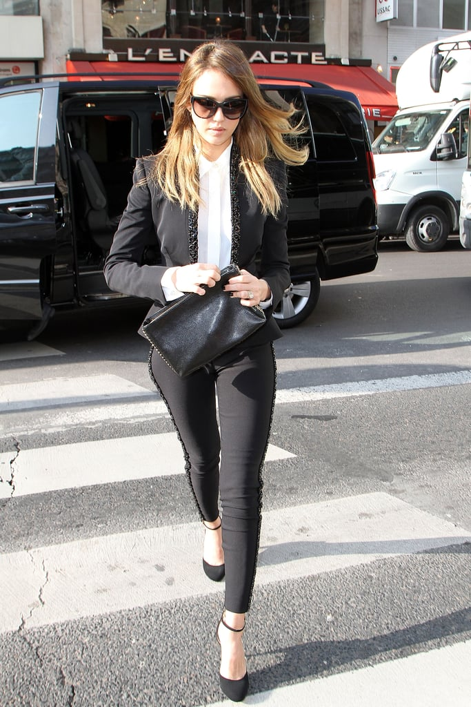 Jessica Alba headed into the Stella McCartney show at Paris Fashion Week in a menswear-inspired black suit with embellishments, finished with a white blouse, ankle-strap pumps, and a Stella McCartney clutch.