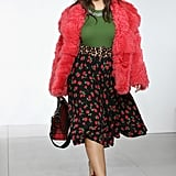 Walking in Michael Kors wearing a fuzzy jacket, green top, and floral skirt.