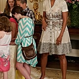 Michelle wore this knee-length, shimmer shirtdress back in 2012, but we love how she paired it with patent leather, pointed-toe pumps for the Annual Mother's Day Tea this year. And she accessorized with one very familiar metallic belt.