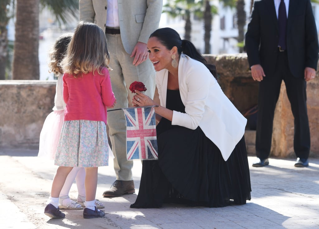 The Duke and Duchess of Sussex's miniature royal tour of Morocco is in full swing, and as ever, the two have been spending a lot of time getting to know the kids who have come out to greet them. Almost every royal engagement gives us a sweet moment between Harry, Meghan, and a group of kids or young people, and we've definitely had no shortage of those on this trip. The royal tour included a trip to Asni, in the foothills of the Atlas Mountains, where Harry and Meghan met teenage girls from rural Morocco who stay at a boarding house in order to attend school nearby. Meghan received a bouquet of flowers from 16-year-old Hasnaa, and also got a henna flower tattoo on her right hand, in celebration of her pregnancy, courtesy of 17-year-old Samira.      Related:                                                                                                           49 Times Prince Harry Was Out-of-Control Cute With Kids               But perhaps one of the sweetest moments came when the couple rushed over to greet two half-Moroccan, half-British girls who were nervously approaching, waving flags from both countries. After shaking their hands and asking their names, Harry commented on their matching red dresses, while Meghan allowed them to admire her henna. Tiny 2-year-old Rayhanna looked completely overwhelmed by the whole experience, as Meghan crouched down to her level.  A similar moment happened the following day, when two more girls were spotted with a banner and flowers, which they happily presented to Meghan as she stopped to say hi. See the sweet moment for yourself ahead, along with lots more pictures of Harry and Meghan with kids during their trip to Morocco.