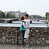 A pair of lovebirds kissed in Paris alongside love padlocks on the Pont des Arts bridge.